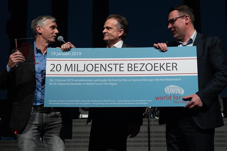 Herre Roelevink uit Pijnacker wordt als 20 miljoenste bezoeker van World Forum The Hague getrakteerd door Wethouder Richard de Mos en General Manager Michiel Middendorf