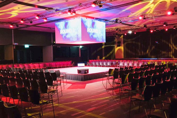 een congres met sprekers in een boxring in het midden van de zaal