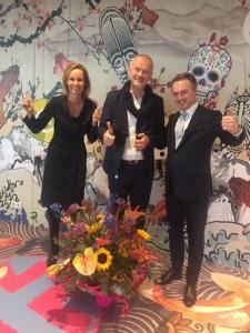 Eline Deijs, Director Marketing & Innovation RAI Amsterdam en RAI-COO Maurits van der Sluis (rechts) feliciteren Hermann Spatt, General Manager nhow Amsterdam RAI.